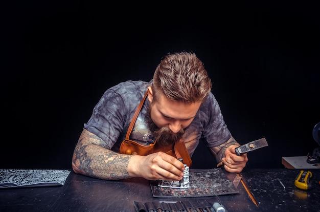 Artista che lavora con la pelle creando un nuovo prodotto in pelle nella conceria. Foto Premium