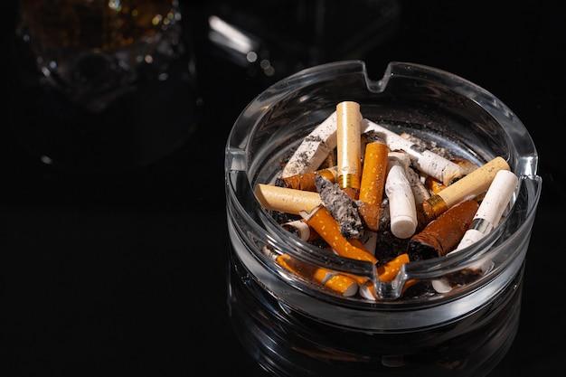 Posacenere pieno di mozziconi di sigaretta su sfondo nero si chiuda Foto Premium