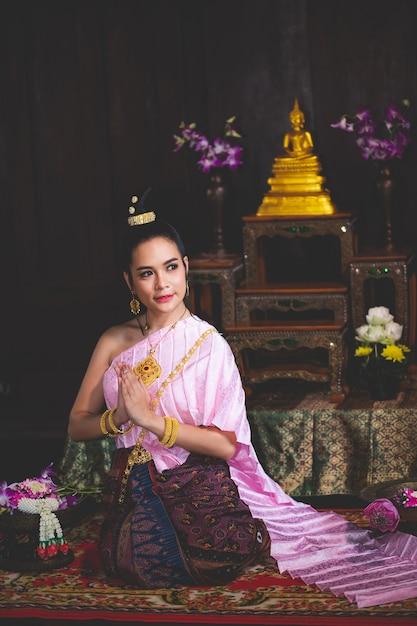 Bella donna asiatica, thailandesi indossava un abito tailandese retrò rosa e riposava le mani nella stanza di preghiera. Foto Premium