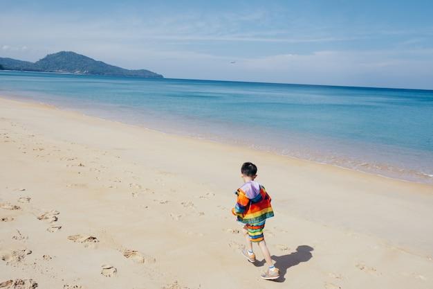 Ragazzo asiatico che cammina sulla spiaggia all'aperto mare e cielo blu Foto Premium