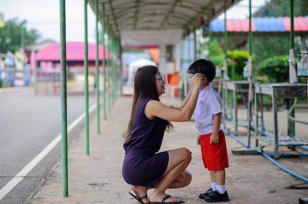 Ragazzo asiatico con la madre che indossa la maschera per la protezione del viso per proteggere da covid-19 Foto Premium