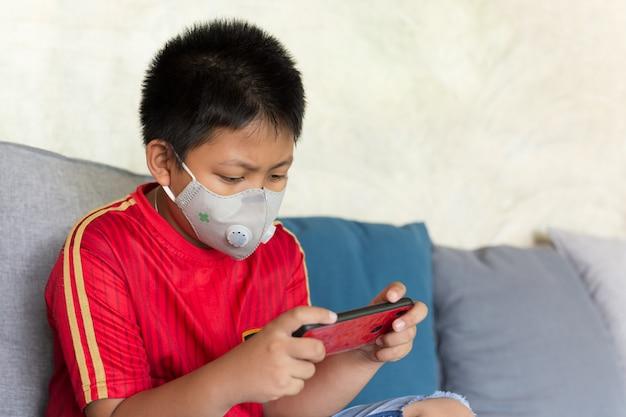 Ragazzo asiatico con la maschera protettiva che gioca gioco sul telefono cellulare a casa. Foto Premium