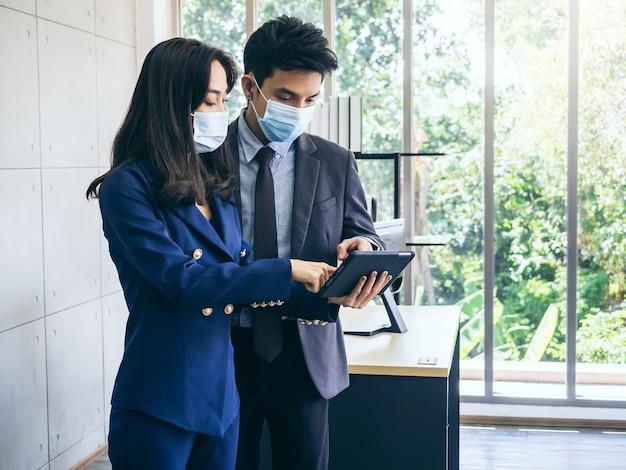 Uomo d'affari asiatico e donna che indossa tuta e maschere protettive utilizzando la tavoletta digitale Foto Premium