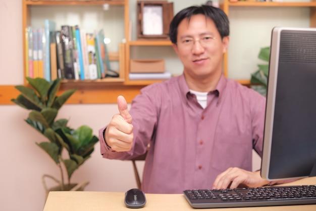 Uomo d'affari asiatico che mostra i pollici in su mentre si utilizza il computer, seduto in ufficio a casa, soluzioni efficaci, raccomandando la scelta migliore per le imprese Foto Premium