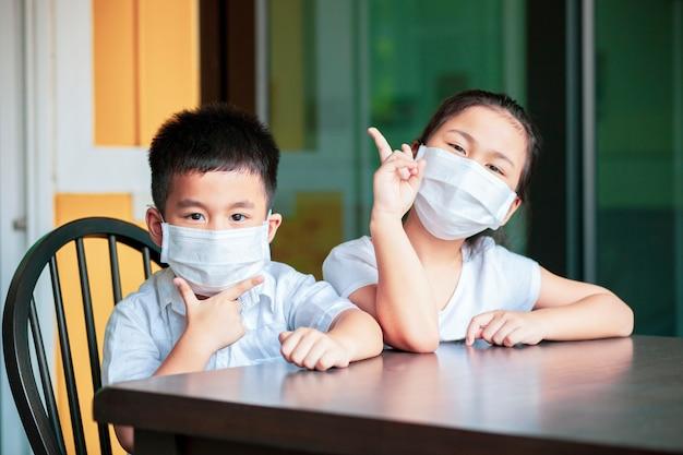 Bambini asiatici che indossano maschera di protezione studiano a scuola a casa Foto Premium