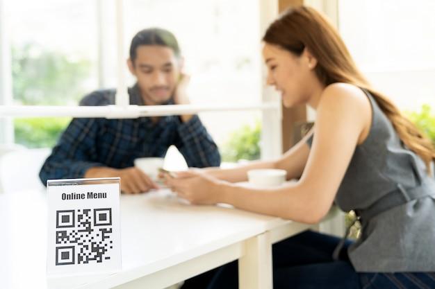 Cliente asiatico che cerca menu online dopo la scansione del codice qr. il cliente si è seduto sul tavolo delle distanze sociali per il nuovo stile di vita normale nel ristorante dopo il coronavirus covid-19 pamdemic. Foto Premium