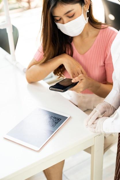 Menu online del codice qr di scansione del cliente asiatico dalla cameriera con maschera e visiera. il cliente si è seduto sul tavolo delle distanze sociali per un nuovo stile di vita normale al ristorante dopo la pandemia di coronavirus covid-19 Foto Premium