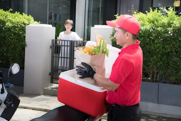 Uomo asiatico di consegna in uniforme rossa che consegna la scatola di generi alimentari di cibo, frutta, verdura e bevande al destinatario della donna a casa Foto Premium