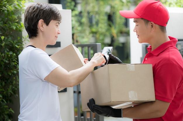 Uomo asiatico di consegna in uniforme rossa che consegna la cassetta dei pacchi al destinatario della donna a casa con il segno del destinatario per ricevere il pacchetto sul dispositivo intelligente Foto Premium