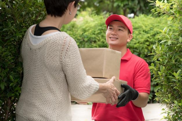Uomo asiatico di consegna in uniforme rossa che consegna la cassetta dei pacchi al destinatario della donna a casa Foto Premium
