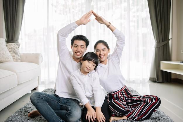 Il ritratto di famiglia asiatico con la gente felice che sorride esamina la macchina fotografica nella casa. Foto Premium