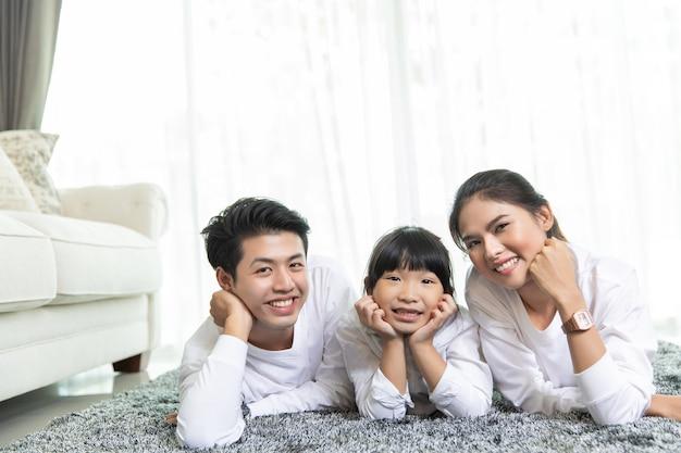 Il ritratto di famiglia asiatico con la gente felice che sorride esamina la macchina fotografica nella mia casa. Foto Premium