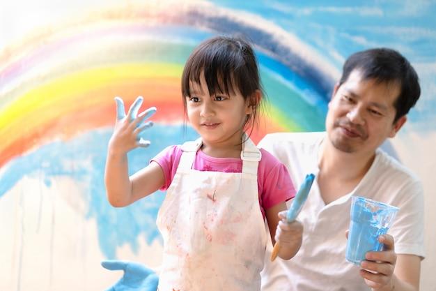 Padre asiatico e figlia che dipingono la parete insieme al momento di piena felicità a casa. Foto Premium