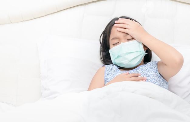 La ragazza asiatica indossa una maschera chirurgica con febbre alta e mal di testa. Foto Premium