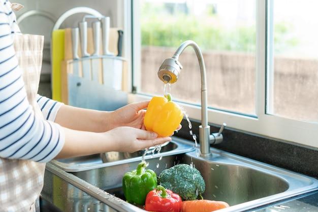 Donna in buona salute asiatica che lava peperone dolce giallo e l'altra verdura sopra il lavandino di cucina Foto Premium
