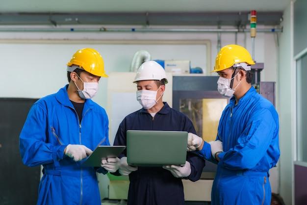 Gli ingegneri industriali asiatici e il lavoratore in elmetti discutono della linea di prodotti nel laptop e fanno gesti dimostrativi e lavorano in una fabbrica di produzione di industria pesante. Foto Premium