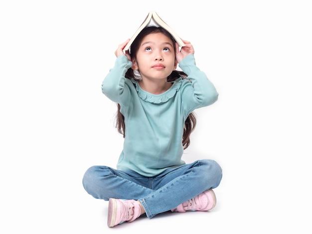 Bambina asiatica carina 6 anni seduto sul pavimento e metti il libro in testa. bambino adorabile prescolare con la copertina del libro sulla sua testa. Foto Premium