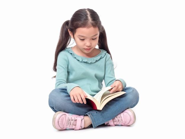 Piccola ragazza sveglia asiatica 6 anni che si siedono sul pavimento e che leggono il libro. bambino adorabile prescolare con il libro. Foto Premium