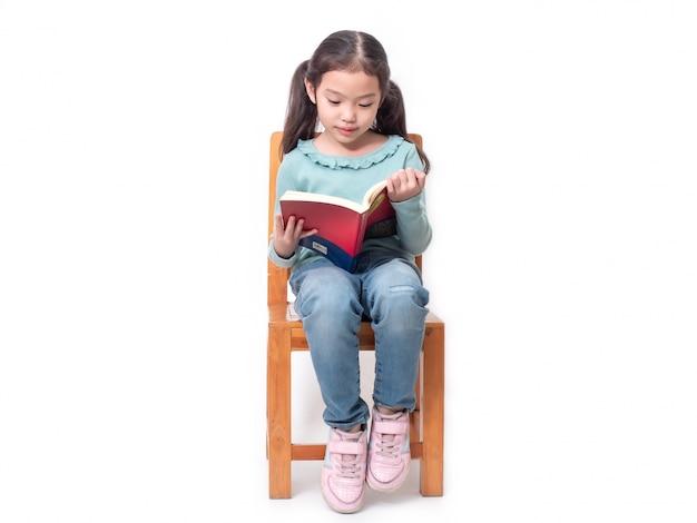 Piccola ragazza sveglia asiatica 6 anni che si siedono sulla sedia di legno e che leggono il libro. Foto Premium