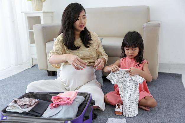 Vestiti e scarpe asiatici del bambino della tenuta della bambina Foto Premium