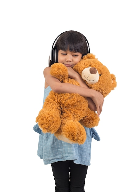 La bambina asiatica sta abbracciando un orsacchiotto su un bianco Foto Premium