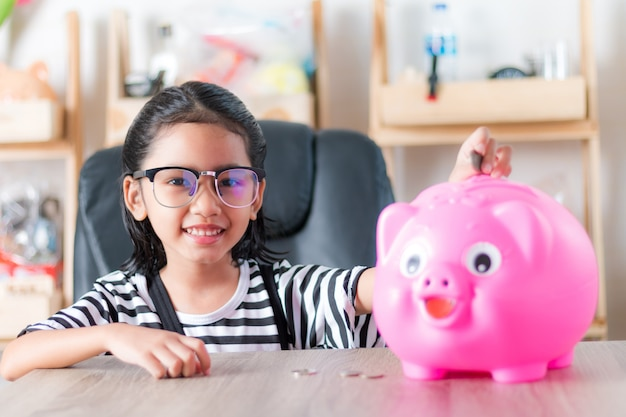 Bambina asiatica nel mettere moneta al fuoco selezionato di profondità di campo bassa del porcellino salvadanaio al fronte Foto Premium