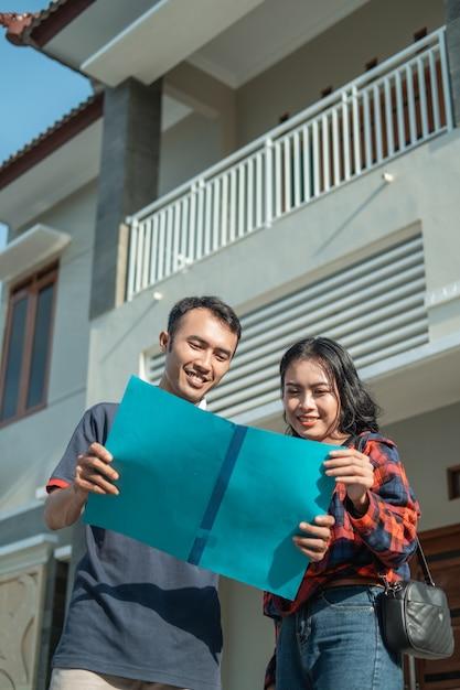 Maschio e femmina asiatici in possesso di un certificato fondiario con una nuova casa Foto Premium