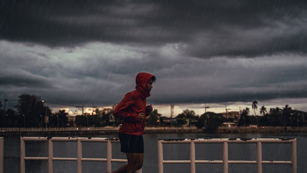 L'uomo asiatico sta praticando la corsa. lui è sotto la pioggia. Foto Premium