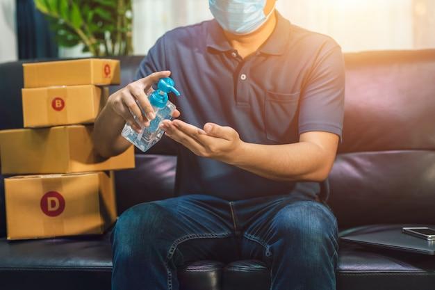 Vendite online dell'uomo asiatico che si lavano le mani con il gel dell'alcool. il venditore prepara la scatola di consegna per il cliente o l'e-commerce. il concetto impedisce la diffusione dei germi ed evita le infezioni covid-19 Foto Premium