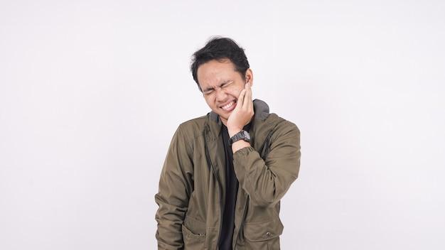 Mal di denti dell'uomo asiatico su uno spazio bianco Foto Premium
