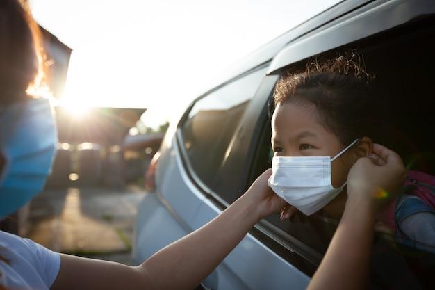 Madre asiatica aiuta sua figlia a indossare una maschera protettiva per proteggere la situazione dell'epidemia di coronavirus covid-19 prima di andare a scuola. preparati al concetto di scuola. Foto Premium