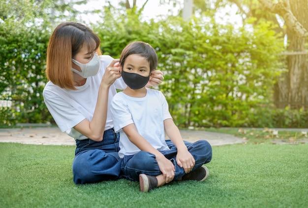 Madre asiatica e suo figlio che indossano maschere protettive Foto Premium