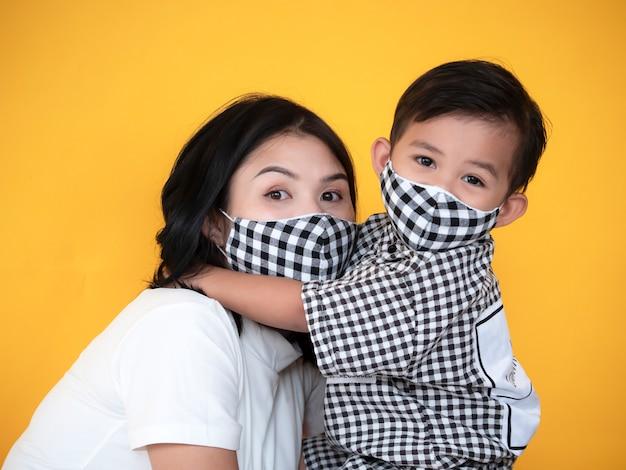 La madre e il figlio asiatici stanno mostrando l'amore e indossano la maschera Foto Premium