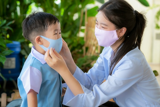 La maschera di protezione asiatica di uso della madre protegge suo figlio prima di andare a scuola materna, questa immagine può usare per il concetto di virus covid19, protezione, famiglia, istruzione e corona. Foto Premium