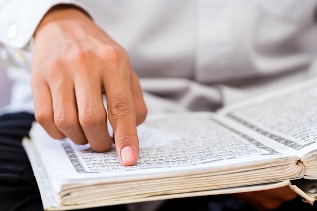 Uomo musulmano asiatico che studia corano o corano Foto Premium