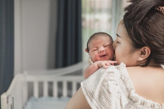 Neonato asiatico con la madre sul letto. mamma che tiene e bacia il suo bambino. Foto Premium