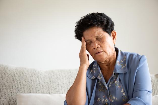 Donna anziana asiatica che si siede sul sofà e che ha un'emicrania Foto Premium