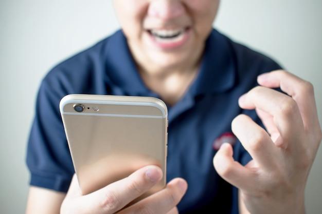 Gli asiatici sono arrabbiati per il messaggio sullo smartphone nella stanza. Foto Premium