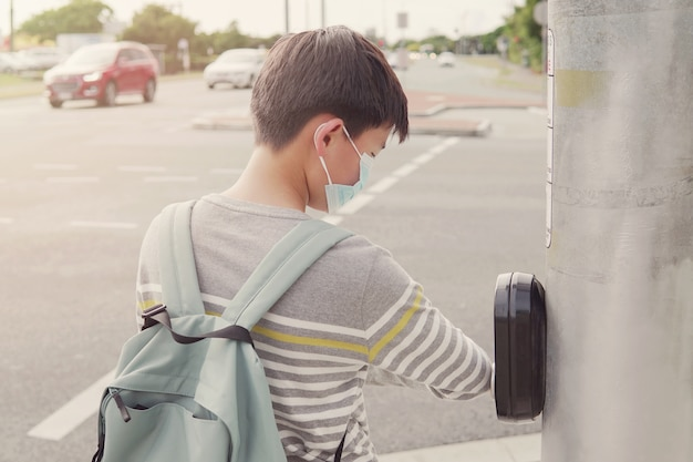 Asian preteen tween teen boy usando il gomito premendo il pulsante del semaforo Foto Premium