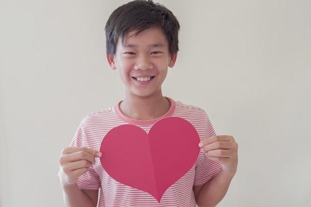 Ragazzo asiatico che tiene grande cuore rosso, salute del cuore, donazione, carità volontaria felice, responsabilità sociale, giornata mondiale del cuore, giornata mondiale della salute, giornata mondiale della salute mentale, benessere, concetto di speranza Foto Premium