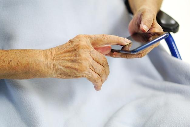 La donna anziana anziana o anziana asiatica sta usando o giocando ai telefoni cellulari, mentre era seduto su una sedia a rotelle. concetto di assistenza sanitaria, medica e tecnologica. Foto Premium