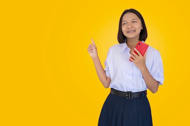 Studente asiatico in uniforme usa smart phone rosso. Foto Premium