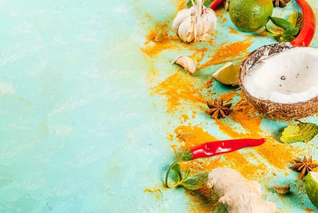 Alimento asiatico e tailandese, cucinante fondo. spezie e ingredienti: cocco, zenzero, peperoncino rosso, lime, curry, menta, spezie. Foto Premium