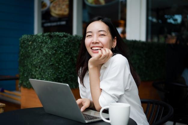 Donna asiatica ad un caffè che lavora ad un computer portatile Foto Premium