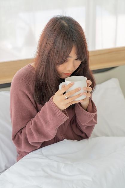 Donna asiatica che beve il caffè sul letto la mattina Foto Premium