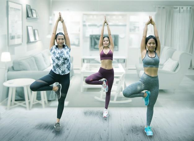 Yoga asiatica di pratica del gruppo della donna a casa Foto Premium