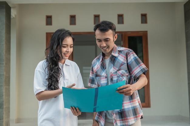 Gesto della mano della donna asiatica che chiacchiera sul certificato di casa con il promotore immobiliare mentre si tiene il certificato di casa davanti alla casa Foto Premium