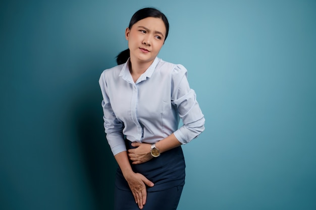Donna asiatica che tiene le mani dolorose premendo il suo addome inferiore del cavallo Foto Premium
