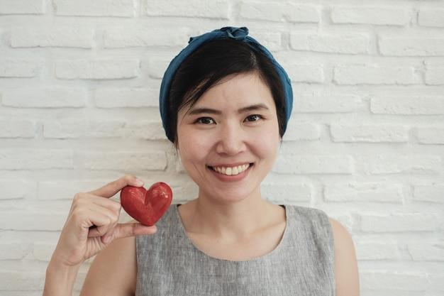 Donna asiatica che tiene cuore rosso, assicurazione sanitaria, carità di donazione Foto Premium
