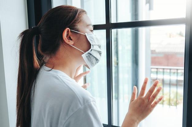 Donna asiatica isolata a casa per lo scoppio del virus coronavirus che indossa una maschera per il viso in quarantena Foto Premium